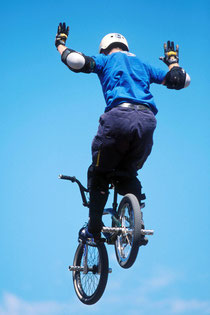 Man on bicycle flying through the air with arms raised praising God