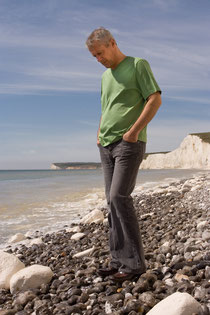 Man standing on beach dressed in jeans and T-Shirt