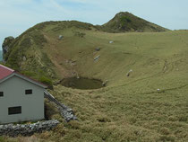 すり鉢状になった山頂、手前は山小屋、池をはさんで見えるのが三嶺山頂