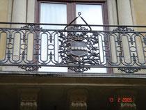 Il balcone centrale con inferriata in ferro battuto e stemma nobiliare. Esterno: sala d'ingresso dello studio.