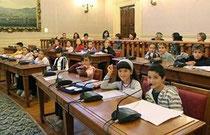 Bambini sui banchi di un consiglio comunale