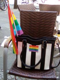 Meine Lieblingshandtasche mit Regenbogenaufkleber und -fahne im Juli 2016 vorm Café Berio.