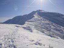 頂上まで続く雪庇の稜線を行く