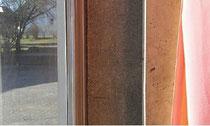 Zwischen Fensterglas und Vorhang befindet sich eine etwa 20 Zentime¬ter breite, fensterhohe Eternit-Platte. Diese Bauteile sind das Problem bei der Schulhaus-Sanierung in Untersteinbach.