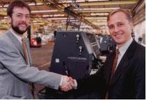 Stolz nimmt OeH-Mitglied Christian Seilnacht (links) im Frühjahr 2002 die Druckmaschine von dem Projektpartner der Heidelberger Druckmaschinen AG in Empfang.