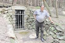 Harald Körner steht vor dem restaurierten Mundloch des Erbstollens bei Steinigtwolmsdorf. Foto: Wolfgang Schmidt