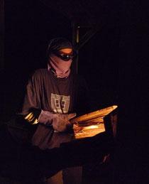 Stoking the wood kiln.