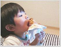 100円お好み焼きを子どもが食べている写真