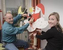 Heimleiter Raimund Haider und Erzieherin Kathrin Glaß dekorieren das Wohnzimmer der Gruppe Drei fürs Weihnachtsfest.
