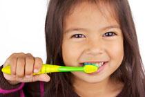 Ein Kind lernt, richtig die Zähne zu putzen