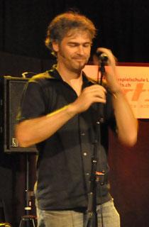 Victor Steiner steht auf einer Konzertbühne und macht sein Mikrophon bereit.