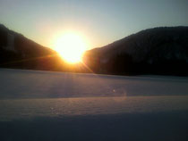雪に埋もれた畑越しに見た夕日