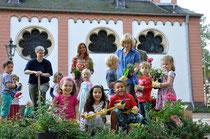 Claudia Hillje, Yvonne Schauch und Elke Bonn (v.l.n.r.) helfen den Kindergarten-Kindern beim Bepflanzen des Hochbeets