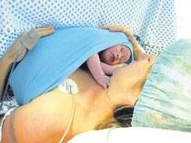 Mit dem wärmenden, haltgebenden Sectio-Top von Hoppediz auf der Brust der Mutter