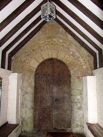 The 12th-century south door with its dog-tooth pattern, enclosed by the 18th-century porch.