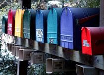farbige Briefkästen in einer Reihe an einem Gartenzaun aufgehängt, Skandinavien