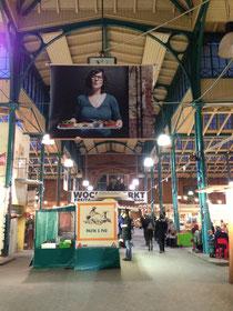Blick von Eingang Pücklerstraße in die Markthalle Neun: Auf einem großen Foto sieht man die Inhaberin mit einem Tablett voller Tapas.