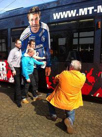 Angeklebt: MT-Torhüter Per Sandström begutachtet sein Konterfei auf der Straßenbahn (rechts) mit Ingo Pijanka (Städtische Werke AG/links) und Klaus Heitmann (Werbetechnik und Messebau) beim Fotoshoot der HNA.
