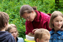 Kinder bestaunen ein gefundenes Vogelnest