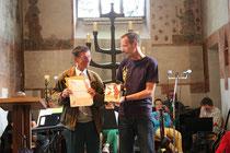 Übergabe von Plakette und Urkunde (links Stefan Heitmann, rechts Pfarrer Kaulisch)