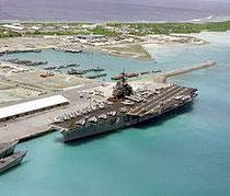 Vue aérienne d'une partie de la base militaire américaine de Diego Garcia montrant le porte-avion USS Saratoga accosté dans le port en 1985.