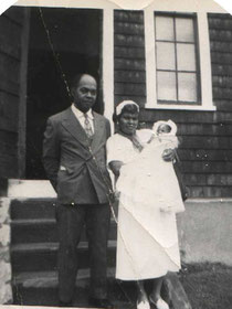 Standing in front of church, Rev. L C Jones, pastor 1933-1938, his wife Susan DaCosta holding their son