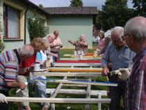 Dutzende begeisterte Senioren beim Holzlatten streichen