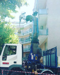 Noleggio camion gru per scarico macerie presso condominio di Rimini