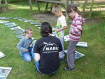 """Ein Mitglied von """"Zukunft Wolf"""" erklärt drei geschminkten Kindern das Spiel Ludus Luporum."""