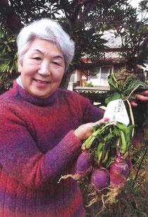 ご自宅の庭で芥屋かぶ色のセーターを身につけ、芥屋かぶを手に持つ東紀子さん。