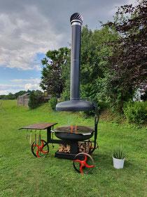 Ein Grill mit einer Feuerplatte, der auch als Feuerschale genutzt werden kann. Mit Zubehör verwandelt er sich in einen Pizzaofen, Smoker oder ist nutzbar für einen Dutch-Oven.