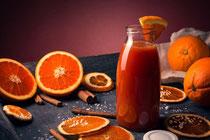Blutorangen-Saft mit Früchten, Zimt und Zucker auf Holztablett vor rotem Hintergrund