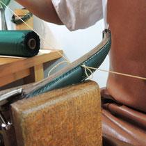 ブリーフケースの持ち手を手縫いしています