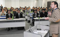被災地で支援活動をした白石院長(右)の報告を聞く参加者=東京都内で