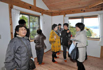完成した復興住宅の室内を眺める入居予定者ら=23日、石巻市北上町十三浜