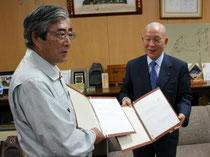 【亀山市長と合意文書を取り交わす北城最高顧問(右)=石巻市役所市長室】