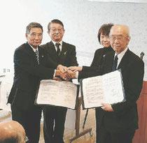 協定書を取り交わす佐藤市長(左)と小川理事長(右)