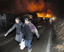 大津波警報が発令され、走って逃げる人たち=仙台市宮城野区で3月11日午後10時1分、丸山博撮影