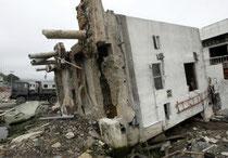 津波で基礎部分のくいごと横倒しになった石巻署女川交番=12日