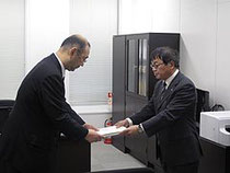 【写真=井上明事務局長に復興推進計画を提出する上野善晴副知事(右)】