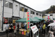 開店を祝う復興市も行われ、多くの客でにぎわった仮設商店街=19日午前、石巻市雄勝町