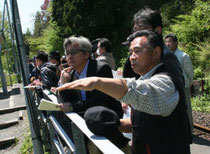両石町地区の被災状況を松尾さん(中央)に説明する松本さん=15日、釜石市