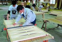 地産材で間仕切りを作る参加者たち=尾鷲市南浦の尾鷲ヒノキ内装材加工協同組合で