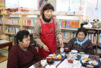 カフェレストランを訪れた被災者に食事を提供する馬場さん(中央)=亘理町下小路