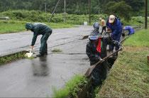 通学路にたまった汚泥などを取り除く住民