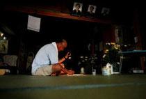 夕暮れ時、懐中電灯の明かりを頼りに家計簿を付ける杉山さん=10日夕、石巻市中央1丁目