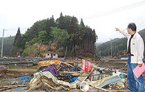 畠山さんらは左奥に見える山に住宅を移転する計画をしている。一帯は津波被害でがれきが散乱する=宮城県気仙沼市で2011年6月2日、樋岡徹也撮影