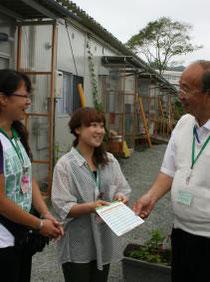 住まいるカードの作成に携わる富沢理事長(右)と仮設住宅の担当職員=亘理町の宮前仮設住宅