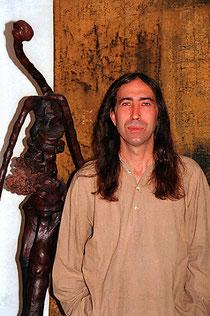 Amador Vallina con una escultura en frente de una pintura