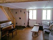Einrichtung des Wohnzimmers mit Klavier und Sofa